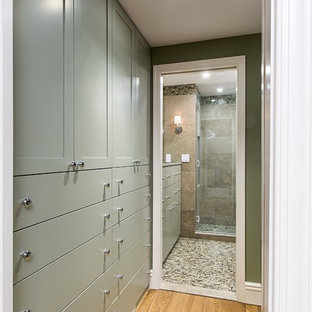 Inspiration for a transitional walk-in wardrobe in New York with recessed-panel cabinets, green cabinets and light hardwood floors.