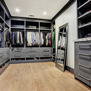 Пример оригинального дизайна: большая гардеробная комната унисекс в стиле современная классика с плоскими фасадами, серыми фасадами, светлым паркетным полом и коричневым полом