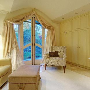 Modelo de armario y vestidor mediterráneo con armarios con paneles empotrados, puertas de armario beige y suelo de piedra caliza
