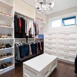 Diseño de vestidor de mujer, clásico renovado, grande, con puertas de armario blancas, suelo de madera oscura y armarios con paneles empotrados