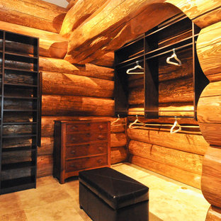 Inspiration for a medium sized rustic gender neutral dressing room in Denver with open cabinets, dark wood cabinets and travertine flooring.