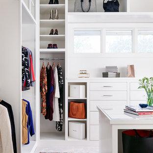 Immagine di una grande cabina armadio per donna contemporanea con ante lisce, ante bianche, moquette e pavimento bianco