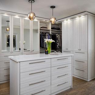 Idee per una cabina armadio unisex chic di medie dimensioni con ante lisce, ante in legno chiaro, pavimento in legno verniciato e pavimento marrone