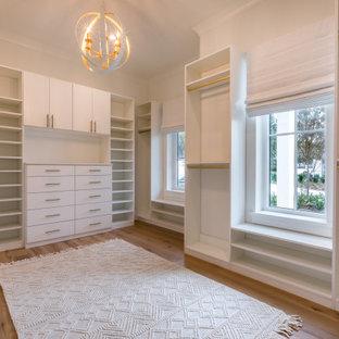 Diseño de armario vestidor de mujer, de estilo de casa de campo, de tamaño medio, con armarios estilo shaker, puertas de armario blancas, suelo de madera en tonos medios y suelo marrón