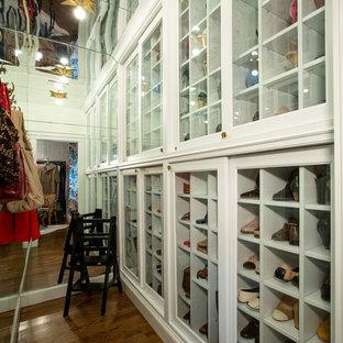 Modelo de armario vestidor de mujer, clásico, grande, con armarios con rebordes decorativos, puertas de armario blancas, suelo de madera oscura y suelo marrón