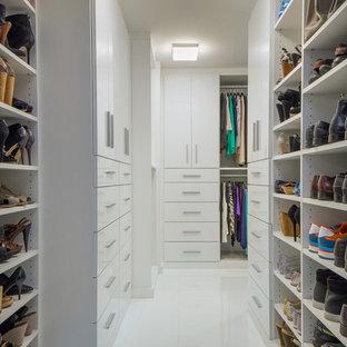 ニューヨークの広い男女兼用コンテンポラリースタイルのおしゃれなウォークインクローゼット (フラットパネル扉のキャビネット、白いキャビネット、白い床、大理石の床) の写真