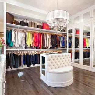 Modelo de vestidor de mujer, tradicional renovado, de tamaño medio, con puertas de armario blancas, armarios abiertos y suelo de madera oscura