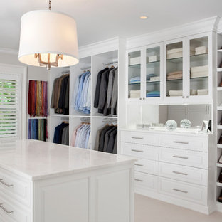 Photo of a large contemporary gender-neutral dressing room in New York with white cabinets, carpet and raised-panel cabinets.
