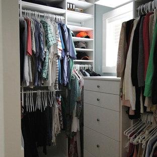 Immagine di un piccolo armadio o armadio a muro unisex con ante bianche e moquette