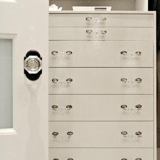 Modelo de armario vestidor clásico, de tamaño medio, con armarios con paneles lisos, puertas de armario blancas y suelo de mármol