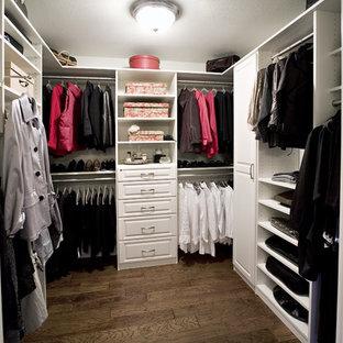 Ejemplo de armario vestidor unisex, clásico, de tamaño medio, con armarios con paneles con relieve, puertas de armario blancas, suelo de madera en tonos medios y suelo marrón