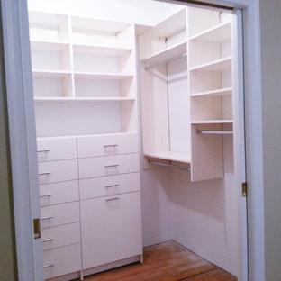 Foto på ett funkis walk-in-closet för könsneutrala, med släta luckor, vita skåp och mellanmörkt trägolv