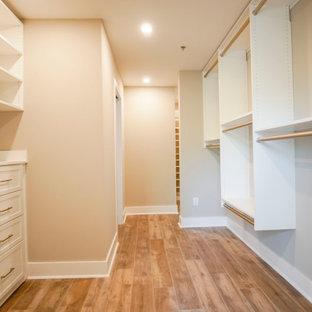 Immagine di una cabina armadio unisex industriale di medie dimensioni con ante con riquadro incassato, ante bianche, pavimento in vinile, pavimento marrone e soffitto in legno