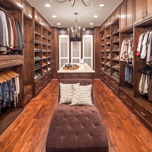 Design ideas for a large traditional gender-neutral dressing room in Houston with recessed-panel cabinets, dark wood cabinets and medium hardwood floors.