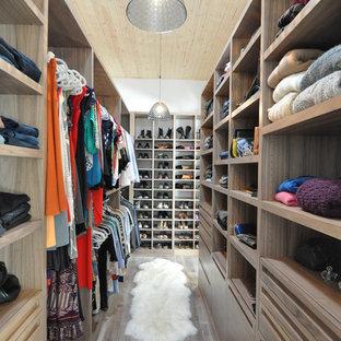 Immagine di un'ampia cabina armadio unisex design con pavimento in legno massello medio, ante lisce, ante in legno scuro e pavimento marrone