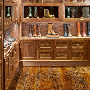 Diseño de armario vestidor clásico, grande, con armarios abiertos, puertas de armario de madera en tonos medios, suelo de madera oscura y suelo marrón