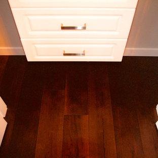 Imagen de armario unisex, moderno, pequeño, con armarios con paneles lisos, puertas de armario blancas y suelo de madera en tonos medios