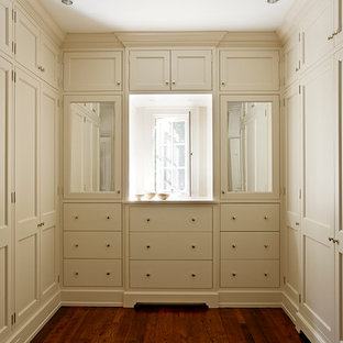 Example of a classic walk-in closet design in Other with recessed-panel cabinets and beige cabinets