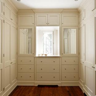 Cette image montre un dressing traditionnel avec un placard avec porte à panneau encastré et des portes de placard beiges.
