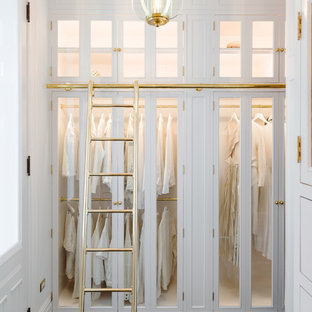 Traditional walk-in wardrobe in New York with glass-front cabinets, white cabinets and dark hardwood floors.