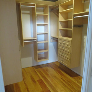 Imagen de armario vestidor unisex, clásico, de tamaño medio, con armarios estilo shaker y suelo de madera en tonos medios