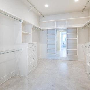 ニューオリンズの大きい男女兼用トランジショナルスタイルのおしゃれなウォークインクローゼット (シェーカースタイル扉のキャビネット、白いキャビネット、大理石の床、白い床) の写真