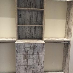 Ejemplo de armario vestidor unisex, rústico, de tamaño medio, con suelo de madera en tonos medios, armarios abiertos, puertas de armario grises y suelo marrón