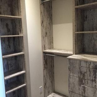 Foto de armario vestidor unisex, rústico, de tamaño medio, con suelo de madera en tonos medios, armarios abiertos, puertas de armario grises y suelo marrón