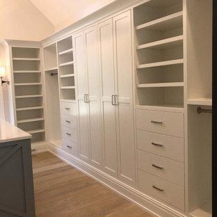 Diseño de armario vestidor unisex, grande, con puertas de armario blancas y suelo de madera clara