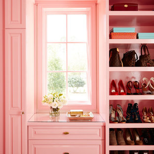 Photo of a mid-sized beach style women's walk-in wardrobe in Jacksonville with raised-panel cabinets.