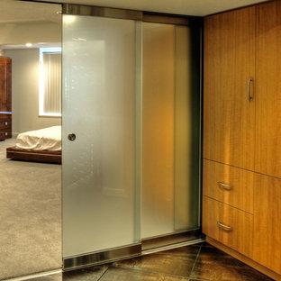 Ejemplo de armario vestidor unisex, actual, grande, con armarios con paneles lisos, puertas de armario de madera clara, suelo de baldosas de cerámica y suelo negro