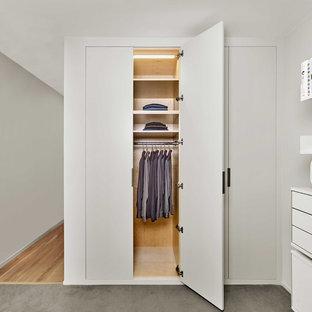 サンフランシスコの中サイズの男女兼用モダンスタイルのおしゃれな壁面クローゼット (フラットパネル扉のキャビネット、白いキャビネット、合板フローリング、グレーの床) の写真