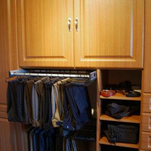 Diseño de armario vestidor unisex, tradicional, grande, con armarios con paneles con relieve, puertas de armario de madera en tonos medios y moqueta