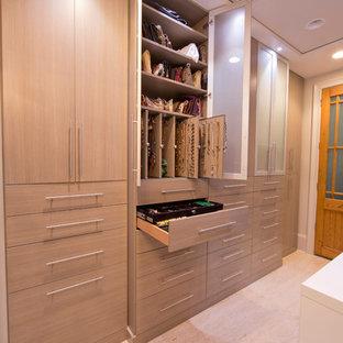 Inspiration pour un très grand dressing room minimaliste pour une femme avec un placard à porte plane, des portes de placard grises et un sol en travertin.