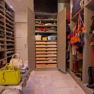 Diseño de vestidor de mujer, minimalista, extra grande, con armarios con paneles lisos, suelo de travertino y puertas de armario beige