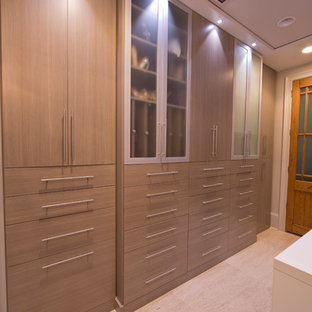 Inspiration for an expansive modern dressing room for women in New Orleans with flat-panel cabinets, travertine flooring and beige cabinets.