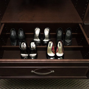 Large traditional gender-neutral walk-in wardrobe in San Francisco with raised-panel cabinets, dark wood cabinets, carpet and multi-coloured floor.