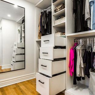Esempio di una cabina armadio unisex minimalista di medie dimensioni con ante lisce, ante bianche, parquet chiaro e pavimento giallo