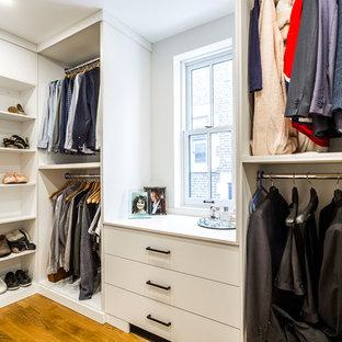 Réalisation d'un dressing minimaliste de taille moyenne et neutre avec un placard à porte plane, des portes de placard blanches, un sol en bois clair et un sol jaune.