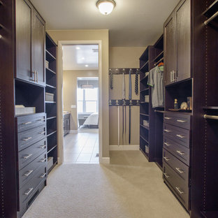 Mid-sized midcentury men's walk-in wardrobe in Denver with shaker cabinets, dark wood cabinets, carpet and beige floor.