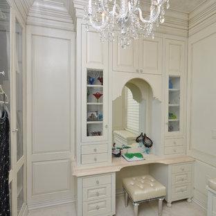 Diseño de armario vestidor de mujer, tradicional, grande, con puertas de armario blancas, suelo de madera oscura y armarios con paneles con relieve