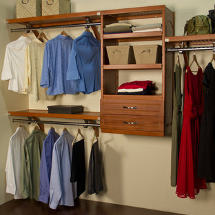 Example of a mid-sized arts and crafts gender-neutral walk-in closet design in Jacksonville with raised-panel cabinets and medium tone wood cabinets