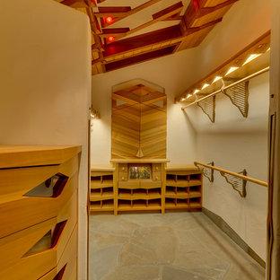 Esempio di un ampio spazio per vestirsi per uomo eclettico con ante di vetro, ante in legno chiaro, pavimento in pietra calcarea e pavimento grigio