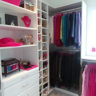 Réalisation d'un grand dressing room design pour une femme avec un placard sans porte, des portes de placard blanches et moquette.