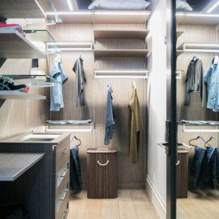 Diseño de armario vestidor de mujer, industrial, de tamaño medio, con armarios con paneles lisos, puertas de armario grises, suelo de madera clara y suelo gris