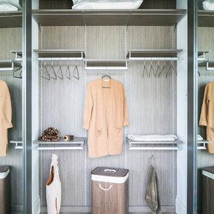 Imagen de armario de mujer, urbano, de tamaño medio, con puertas de armario grises, suelo de madera clara y suelo gris