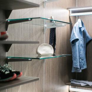 Foto de armario vestidor de mujer, industrial, de tamaño medio, con puertas de armario grises, suelo de madera clara, suelo gris y armarios con paneles lisos