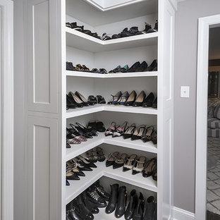 Klassisk inredning av ett litet walk-in-closet för könsneutrala, med luckor med infälld panel, vita skåp, mörkt trägolv och brunt golv