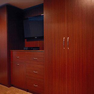 Ejemplo de armario de hombre, actual, de tamaño medio, con armarios con paneles lisos, puertas de armario de madera oscura, moqueta y suelo beige