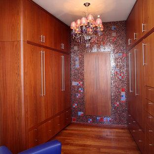 Ejemplo de armario vestidor contemporáneo con puertas de armario de madera oscura